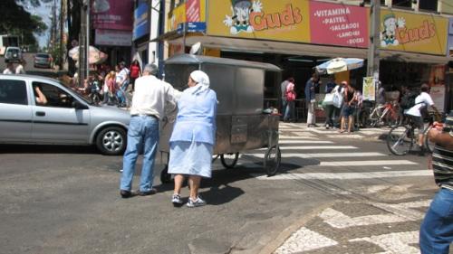 Perto do Terminal Urbano, o carrinho de lanches é empurrado por dois idosos em meio ao trânsito. Crédito: Vitor Oshiro